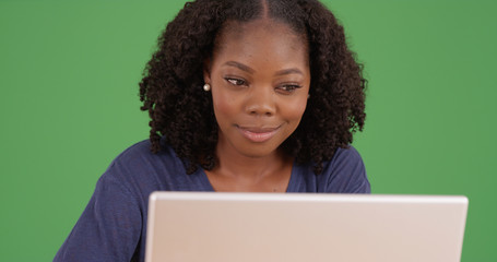 African American woman working on laptop computer on green screen