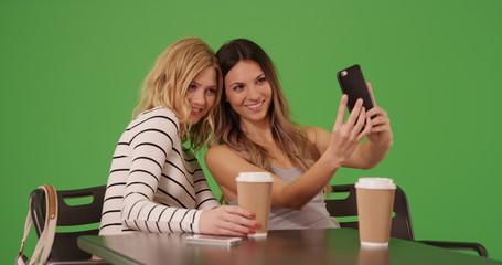 Portrait of two happy female friends sitting taking selfie on green screen