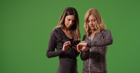 Young attractive fitness women looking at their smartwatches on green screen