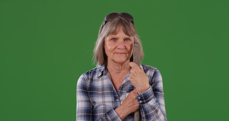 Elderly farm woman standing with tool handle looking at camera on green screen