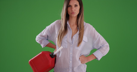 Millennial woman holding red gasoline can with hands on hips on green screen