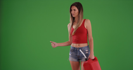 Beautiful white female hitchhiking after running out of gas on green screen
