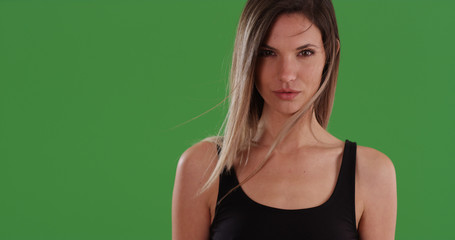 Serious looking white woman in black top looking at camera on green screen