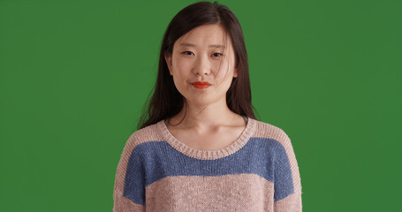 Young Asian woman standing wearing sweater on green screen