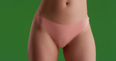 Close up portrait of young woman's hips and thighs on green screen