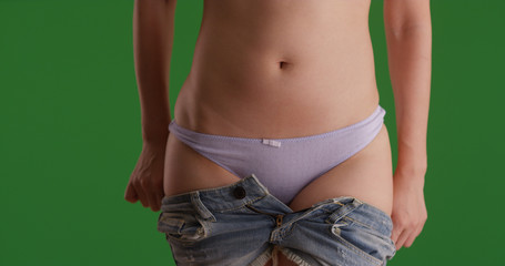 Attractive slim woman taking her blue jeans off on green screen