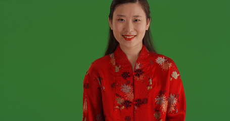 Lovely Chinese female wearing traditional outfit smiling on green screen