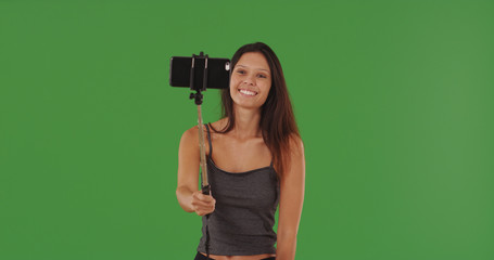 Cute girl using smartphone with selfie-stick to take selfie on green screen
