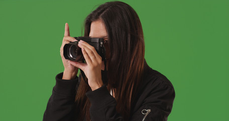 Female photographer taking picture with dslr camera on green screen