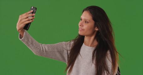 Beautiful white woman taking selfies with smartphone on green screen