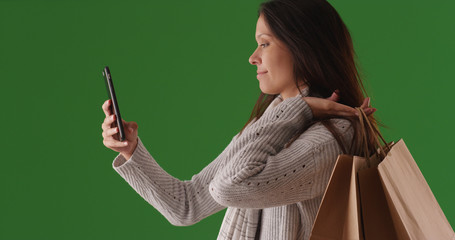 Profile portrait of female shopper taking selfie with phone on green screen