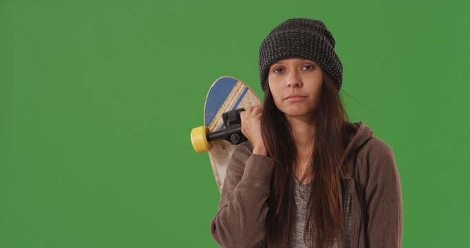 Casual young female skateboarder with board posing on green screen