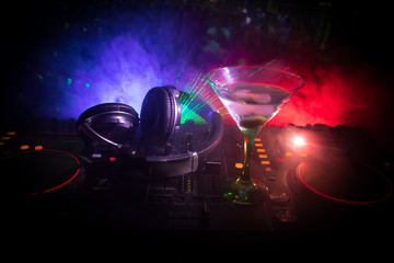 Glass with martini with olive inside on dj controller in night club. Dj Console with club drink at music party in nightclub with disco lights. Close up view