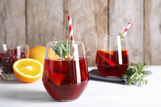 Tasty refreshing cranberry cocktail with rosemary on table
