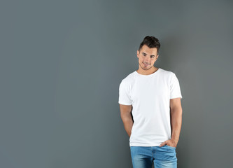 Young man in t-shirt on grey background. Mockup for design