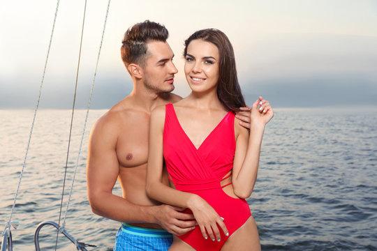 Young man and his beautiful girlfriend in bikini on yacht. Happy couple during sea trip