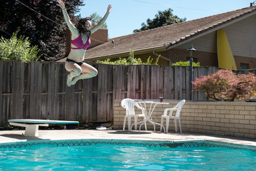 Young brunette woman jumps off diving board arms up in the air into an outdoor swimming pool. Hooray arms up excitement as white girl jumps off diving board into a swimming pool in the summer.