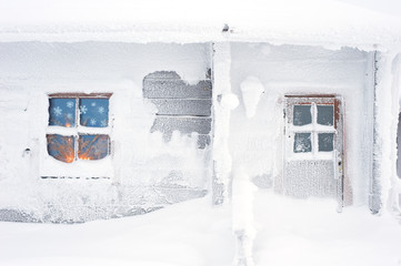 Cottage covered with snow in winter. Candlelight glowing through frosty window.