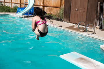 Young brunette jumping off a diving board into an outdoor swimming pool. Woman in black and pink bikini doing caught in mid air doing a cannon ball into a private swimming pool in the backyard.