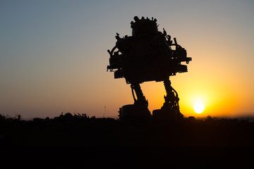 Silhouette of giant robot. Futuristic tank in action at sunset.