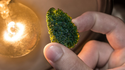 Moldavite. Green mineral of meteoritic origin. Close-up of rare tektite. Vitreous silica rock of raw rough surface in human hand. Collector's piece found near Vltava river, Czech Republic, Europe.
