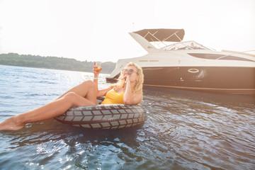Красивая девушка плавает на надувном кругу, на заднем фоне плывет яхта, девушка пьет шампанское