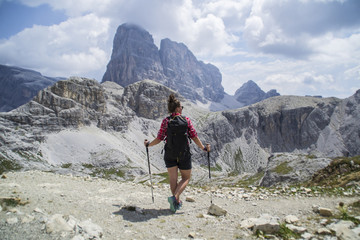 Young active hiker tourist man walking/hiking Tre Cime di Lavaredo trail in Dolomites, Italy, Europe. Beautiful mountain scenic landscape view. Summer outdoor activity or active holiday concept.