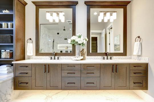 Master bathroom interior in luxury modern home with dark hardwood cabinets, white tub and glass door shower