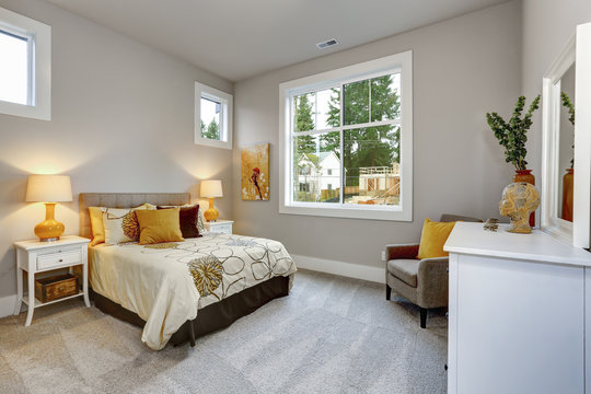 Guest modern bedroom interior with grey walls and orange pillows