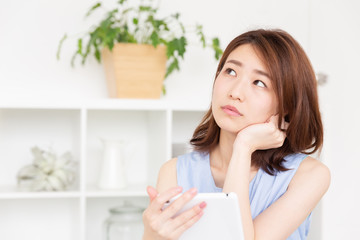 部屋でタブレットを見る女性 考える