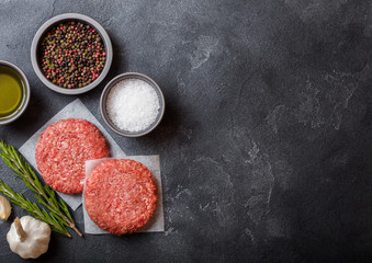 Raw minced home made grill beef burgers with spices and herbs. Top view with space for your text