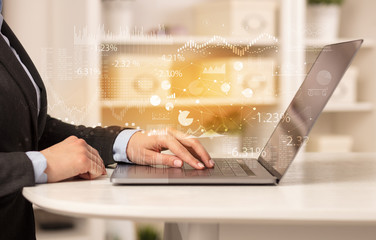 Business woman in homey environment using laptop with financial report concept