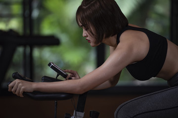 Slide view of fitness woman exercising with  running on treadmill machine in gym; concept for exercising indoor.