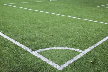 Corner kick line of football and soccer field, artificial green grass texture on soccer stadium. Sport concept. Closeup