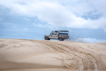 A old truck driving through the unique white sand dunes in a cloud day in the Lencois Maranhenses in north Brazil