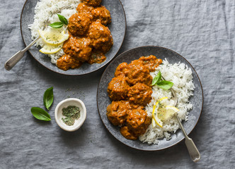Lentils vegetarian roasted meatballs with curry sauce and rice - healthy lunch on grey background, top view. Flat lay