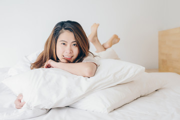 Happy Asian woman lying on bed with crossed legs and looking to camera.