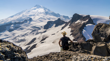 Beautiful panorama of a glacier, snowy mountain peak in the background, hiker wearing a backpack and a straw hat standing on the cliffs, admiring the beauty of nature. Mount Baker, Washington, USA.