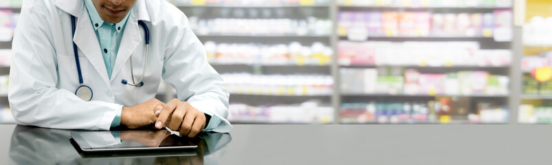 Pharmacist with tablet computer at pharmacy.