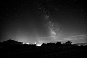 Beautiful view of starred night sky with milky way over a cultivated field Assisi town (Umbria, italy) in the background