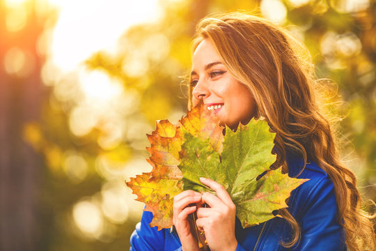 Cute smiley woman holding autumn leafs in the nature.