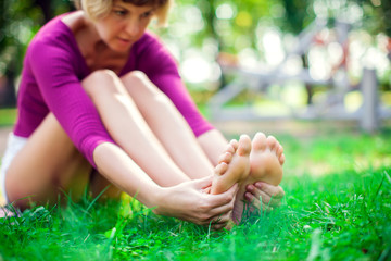 Young woman feeling pain in her foot during sport workout in the park. Sport, medicine and people concept