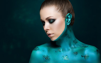 attractive model with creative makeup. The skin is painted in pearl-turquoise paint.