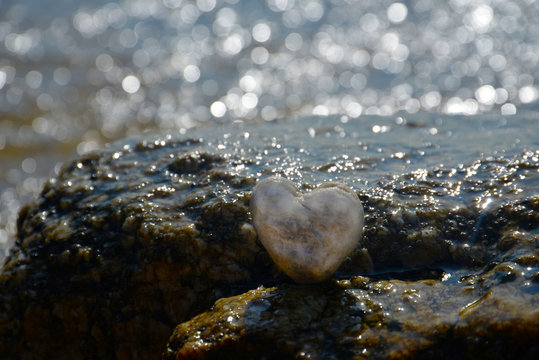 Heart shape stone on the rock at the beach, summer background