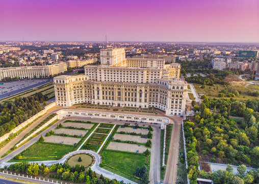 Parliament building or People's House in Bucharest city. Aerial view at sunset with abstract pink sky