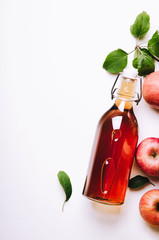 Apple vinegar in bottle on white wooden table with apples and leaves. Rustic style. Top view, copy space.