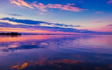 Beautiful pink sunset over lake. Nature landscape panorama