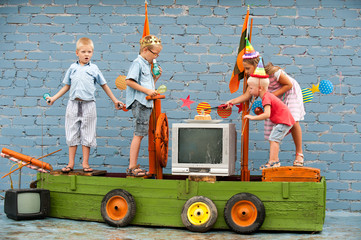 Happy Brothers-boys in colored clothes and girl celebrate birthday of youngest boy on pirate ship. Girl and boy are dressed in carnival hat for parties. Children are happy together. 3 years old