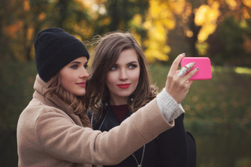 Lifestyle image of best friend girls taking selfie on smartphone camera outdoors, emotions and happy vacations.