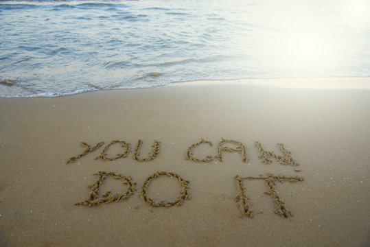 You can do it. Motivational inspirational message concept written on the sand of beach